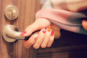 ドアノブを持つ女性の手