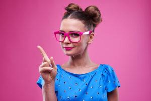 人差し指を立てるメガネをした女性